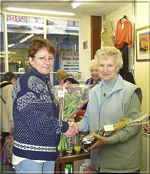 Marianne Smith of Danica Florists in Castletown presents Anne Clague with a bouquet and bottle of wine.